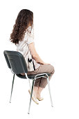 back view of young beautiful  woman sitting on chair.  girl  watching. Rear view people collection.  backside view of person.  Isolated over white background.