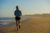 back view of young happy and attractive fit woman in hoddie running on the beach in outdoors jogging workout in fitness training and healthy sporty lifestyle concept