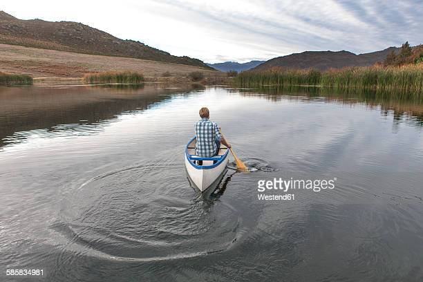 Back view of young man paddling on a lake