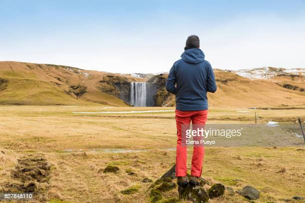 Back view of young man standing on rock looking at Skogafoss waterfall, Iceland