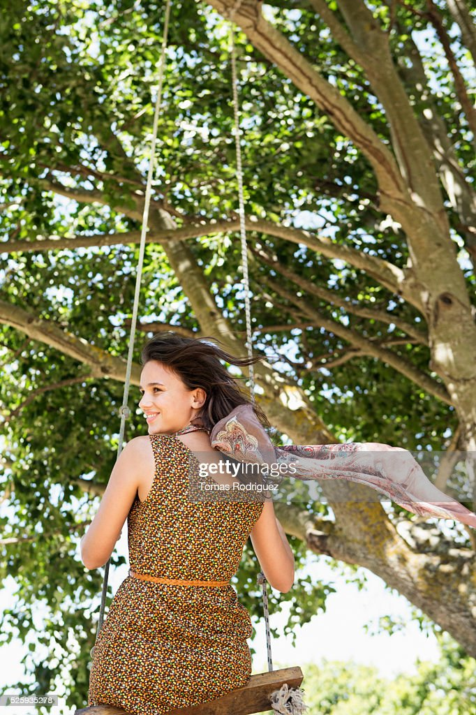 Back view of young woman on swing : Stock Photo