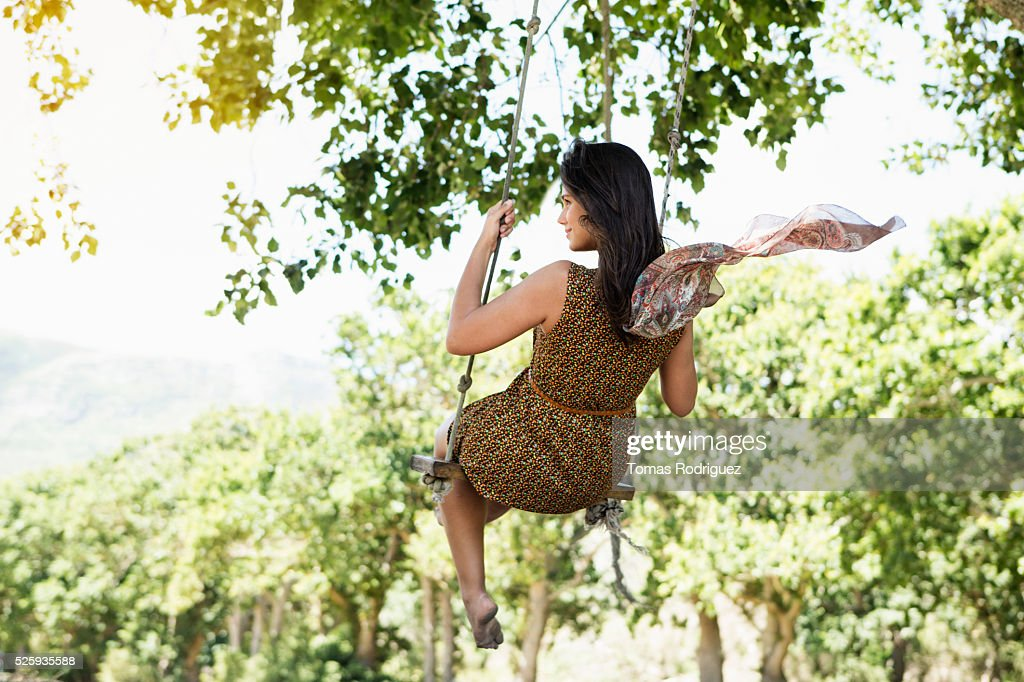 Back view of young woman on swing : Foto de stock