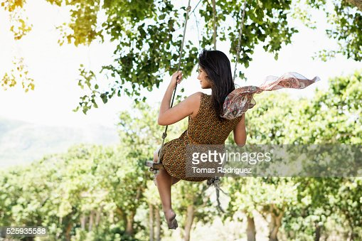 Back view of young woman on swing : Foto stock