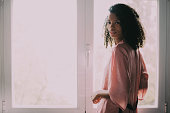 pretty black woman standing at the window