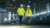 Back View Shot of Male and Female Industrial Engineers Having Discussion While Walking Through Heavy Industry Manufacturing Factory. Big Metalwork Constructions, Pipeline Elements Lying Around.