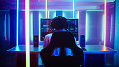 Back View Shot of the Beautiful Professional Gamer Girl Putting on Headset and Starts Playing Online Video Game on Her Personal Computer. Cute Casual Geek Girl. Room Lit by Neon Lamps in Retro Arcade