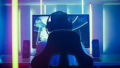 Back View Shot of the Professional Gamer Playing in First-Person Shooter Online Video Game on His Personal Computer. Room Lit by Neon Lights in Retro Arcade Style. Online Cyber e-Sport Internet Champi