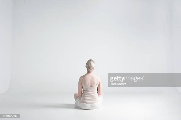 back woman sitting cross legged in white studio