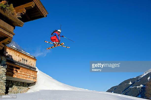 Backcountry skier jumping of ski lodge. Mute grab.