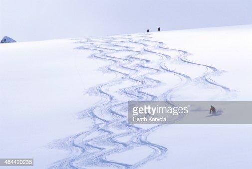 Backcountry skier matching tracks downhill.