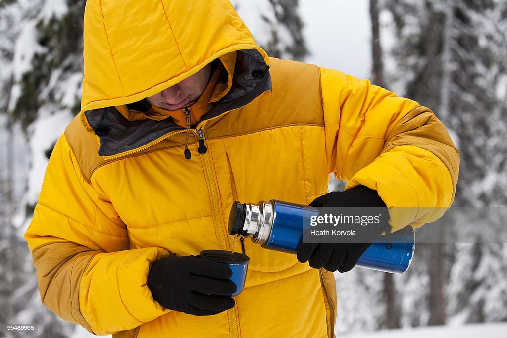 Backcountry skier pouring hot drink. : Stock Photo