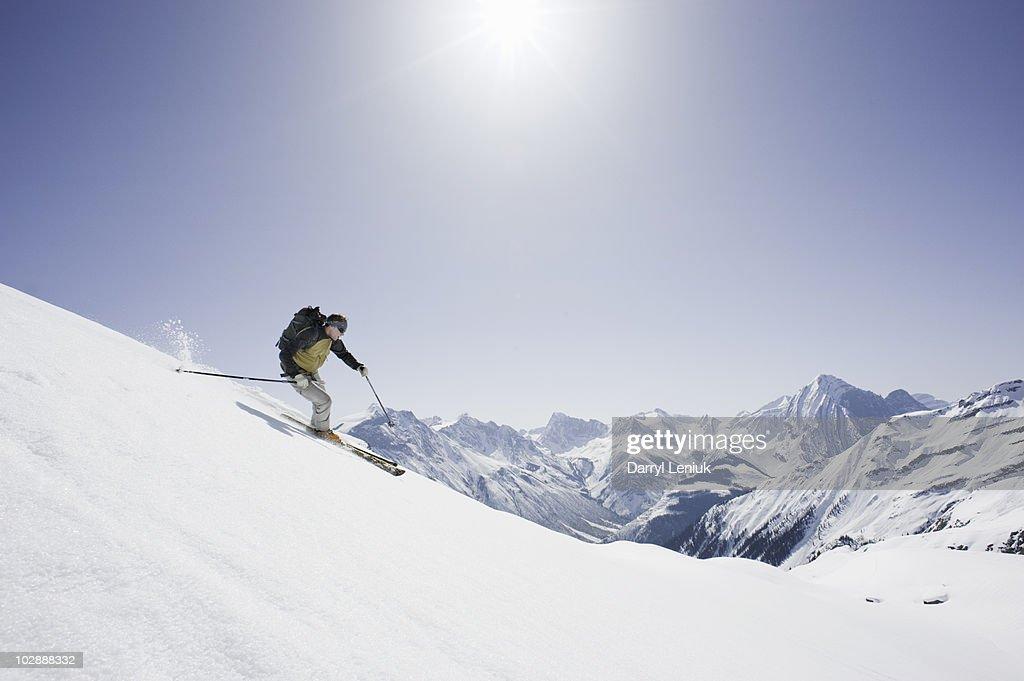 backcountry skier skiing down mountain : Stock Photo