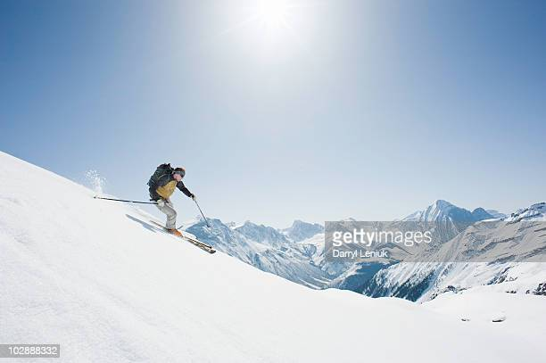 backcountry skier skiing down mountain