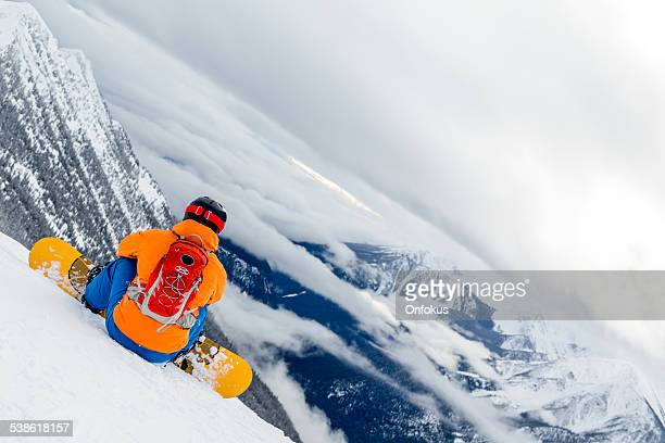 Backcountry snowboarder on Mountain Summit and looking at the cliff
