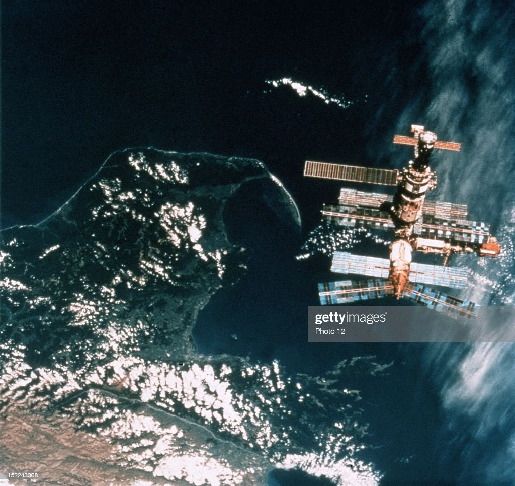 Backdropped against the waters of Cook Strait near New Zealand's South Island Russia's MIR Space Station is seen from the aft flight deck of the...
