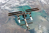 Backdropped by a colorful Earth, this full view of the International Space Station was photographed from the Space Shuttle Discovery during the STS-114 Return to Flight mission, following the undocking of the two spacecraft.