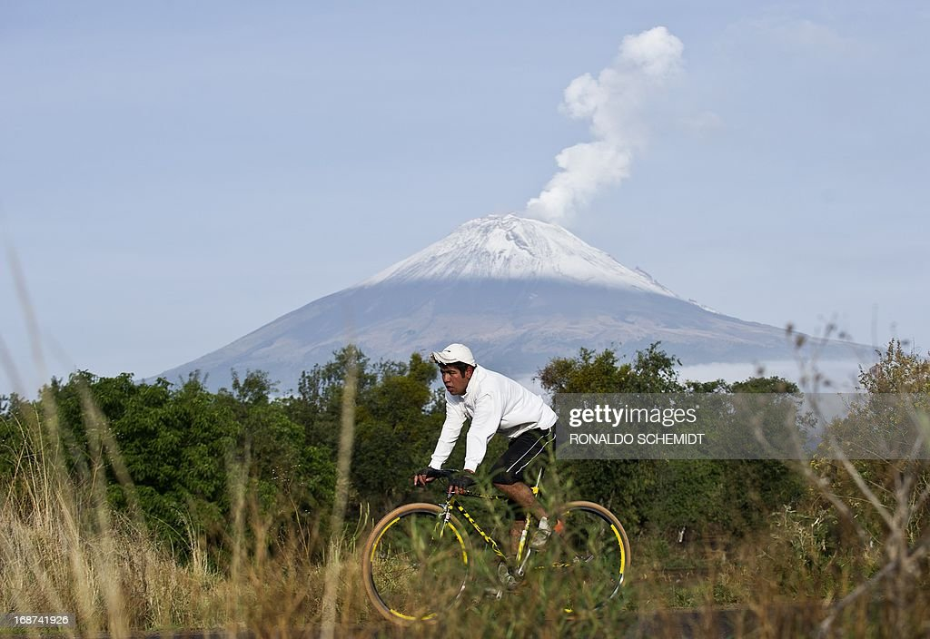 Backdropped by Popocatepetl Volcano, Mexico's second highest peak just 55 km southeast of Mexico City, a man rides his bicycle in San Nicolas de los Ranchos, in the state of Puebla, on May 14, 2013. The National Disaster Prevention Centre (CENAPRED) raised the alert level on Sunday to 'yellow phase three' as the Popocatepetl continues to spew ash and smoke.