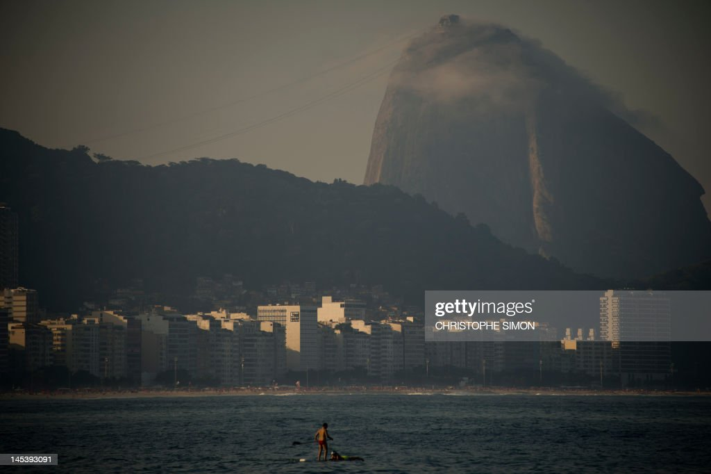Backdropped by the sugar loaf, a couple enjoys the afternoon on a stand up paddle at Copacabana beach in Rio de Janeiro on May 27, 2012. AFP PHOTO/Christophe SIMON
