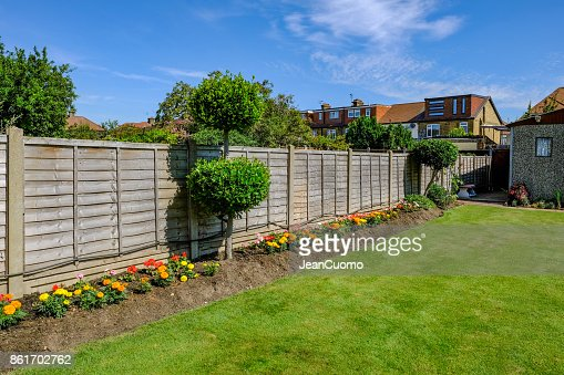 Backgarden flower bed with fence : Stock Photo