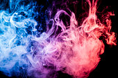 Thick colorful smoke of red and blue on a black isolated background. Background from the smoke of vape