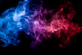 Thick colorful smoke of pink, red and blue on a black isolated background. Background from the smoke of vape