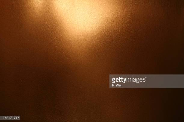 Background: gold/copper metallic surface
