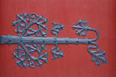 Detail of an old red door with wrought iron decorations