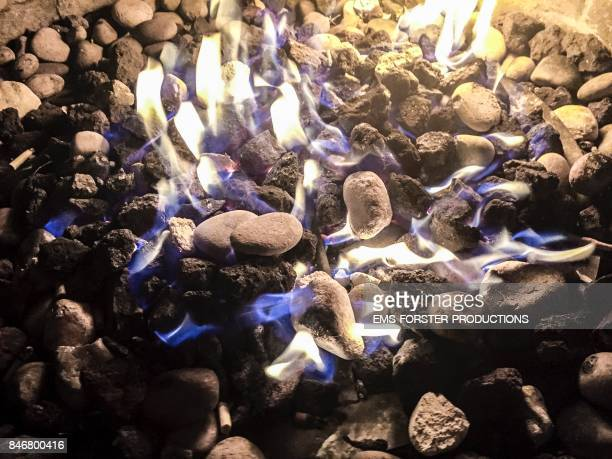 Background of burning fire flames stones and charcoal in fire bowl brazier during night