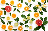 Colorful pattern made of slices of citrus fruits (orange, lemon, lime, grapefruit) and green leaves isolated on white background.