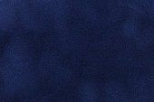 Background of dark blue suede fabric closeup. Velvet matt texture of navy blue nubuck textile.