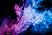 Dense multicolored smoke of   blue, and pink colors on a black isolated background. Background of smoke vape