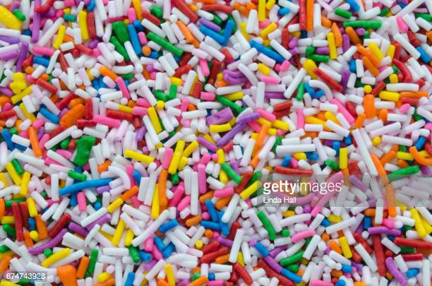 Background of sprinkles in a rainbow of colors.