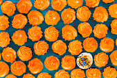 Background pattern of glazed orange cupcakes with one single different cookie with white icing and sprinkles viewed full frame from above in a conceptual image