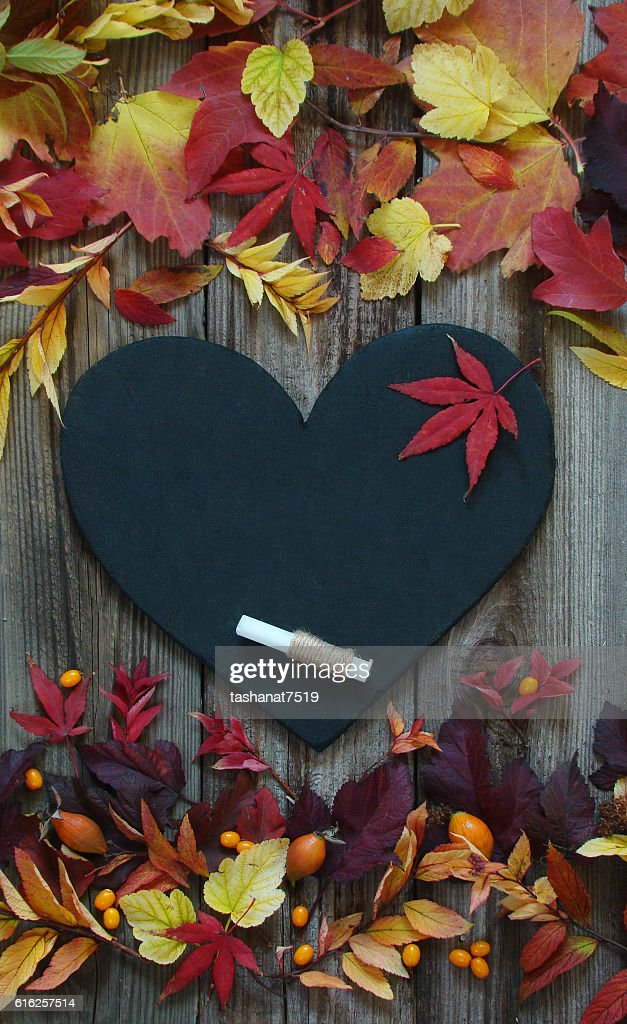 Background with autumn leaves, slate heart and chalk : Foto de stock