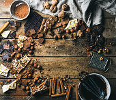 Background with chocolate. Pieces of white, dark and milk chocolate, nuts, cocoa powder, melted chocolate and spices. Hot chocolate cooking ingredients. Rustic wooden background, top view, copy space