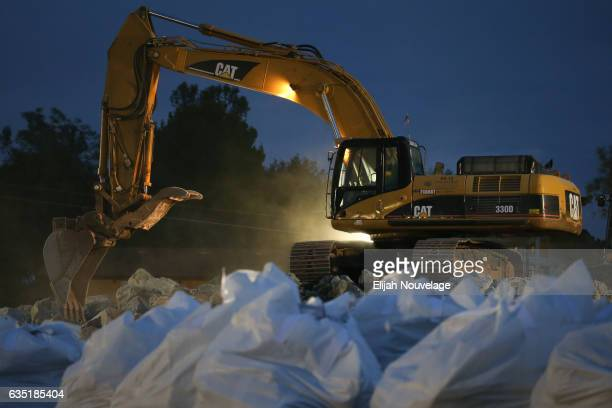 A backhoe collects boulders to load into a dump truck as bags of rocks await pickup by helicopters at Oroville Lake on February 13 2017 in Oroville...