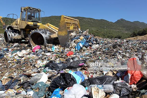 Backhoe loader tractor moves garbages and rubbish on a landfill site on September 1 at Propriano on the French Mediterranean island of Corsica The...