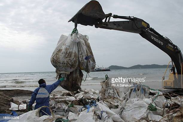 A backhoe removing bags of crude oil mopped up from Ao Phrao beach on Samed island Workers from the Thai oil company PTT along with Thai military...
