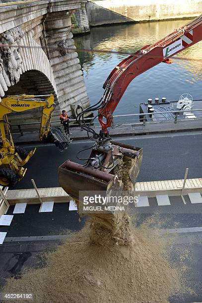 A backhoe unloads sand from a barge as workers prepare to set up an artificial beach on the banks of the Seine on July 17 2014 in Paris as part of...