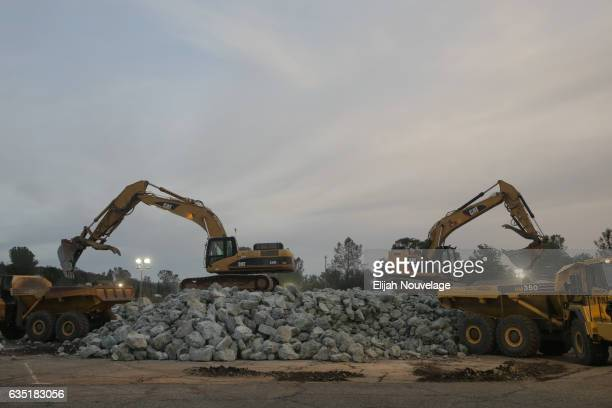 Backhoes load boulders into dump trucks as emergency personnel work to fix the damage below the emergency spillway at Oroville Lake on February 13...