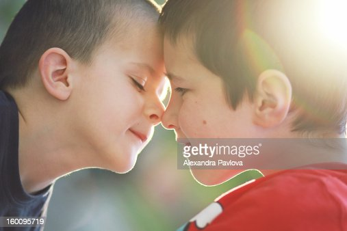 backlight portrait of children rubbing noses