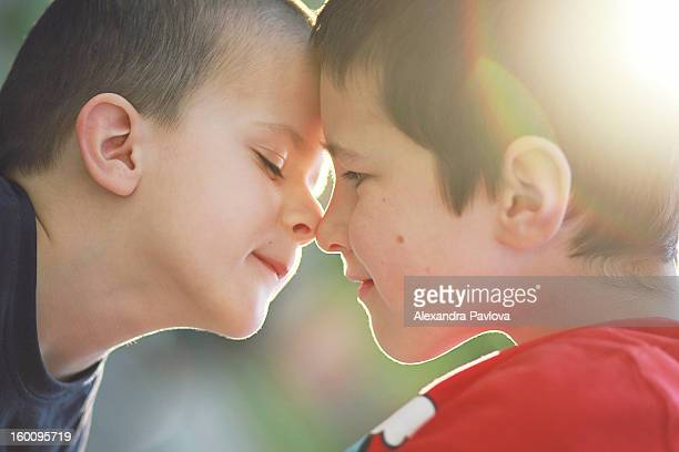 backlight portrait of children rubbing noses