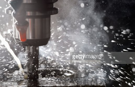 Back-lit CNC milling machine in operation cutting steel