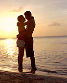 Backlit couple embracing on beach