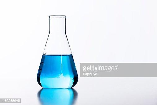 Backlit glass lab flask half filled with blue liquid