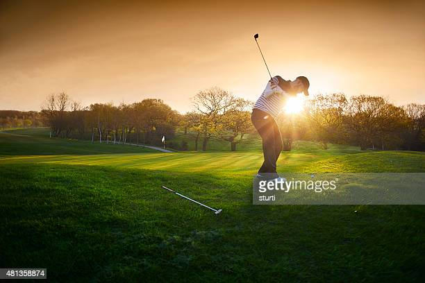 backlit golf course with golfer chipping onto green