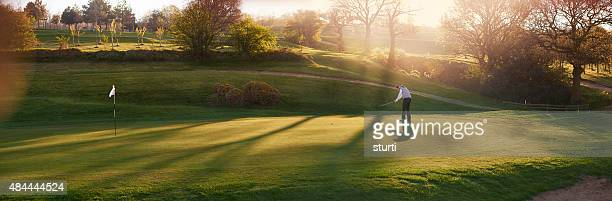 backlit golf course with golfer putting on a green