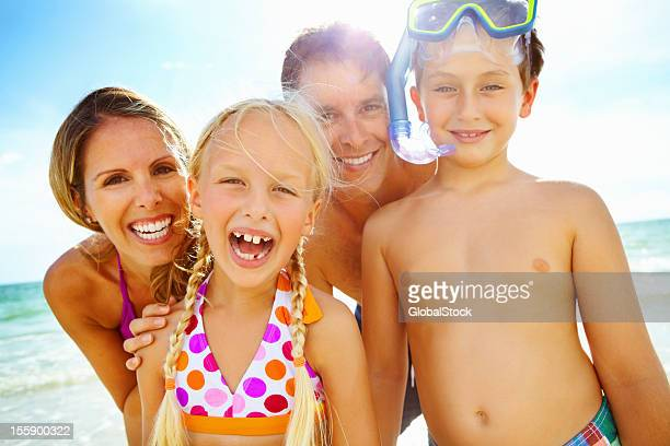 Backlit happy family in bathing suits on the beach