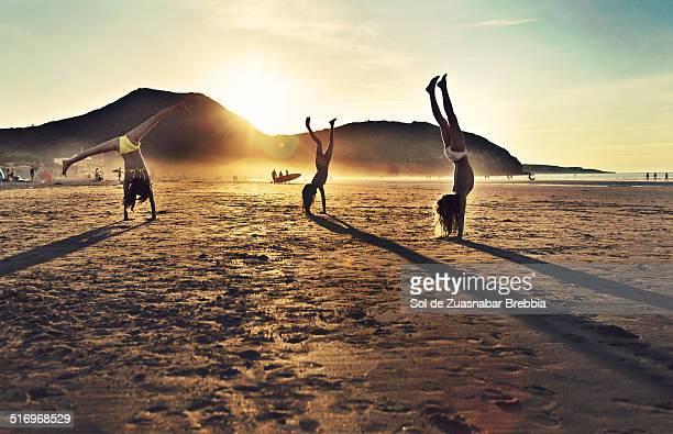 Backlit image of girls doing gymnastics at beach