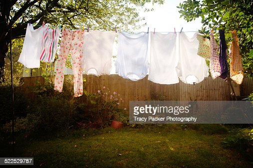 Backlit laundry hangs on a washing line.